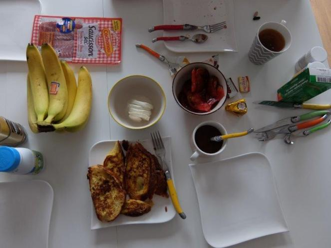 Breakfast table with saucisson french toast coffee mozarella tomatoes and bananas