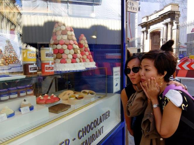 Two girls looking at colorful macarons