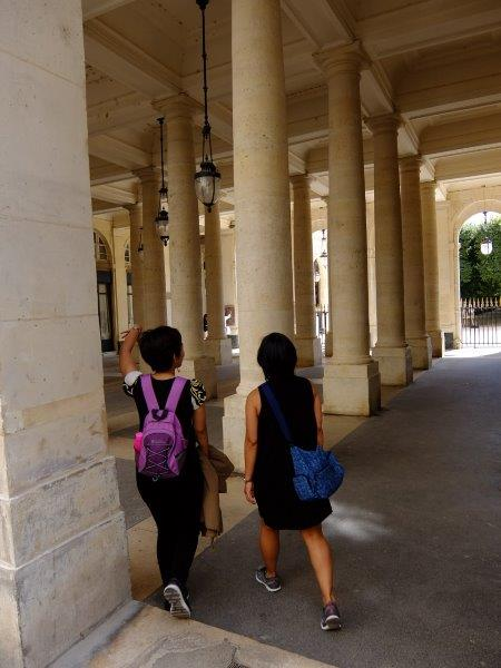 two girls walking through column lined pathway
