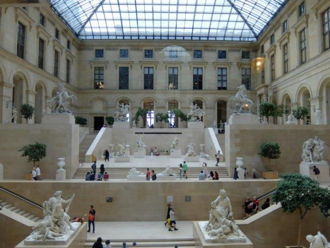Statues and sculptures and tourists inside the louvre