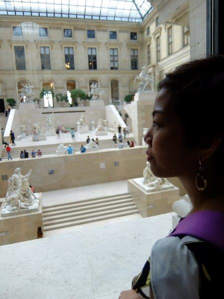 Statues and sculptures and tourists inside the louvre girl watching