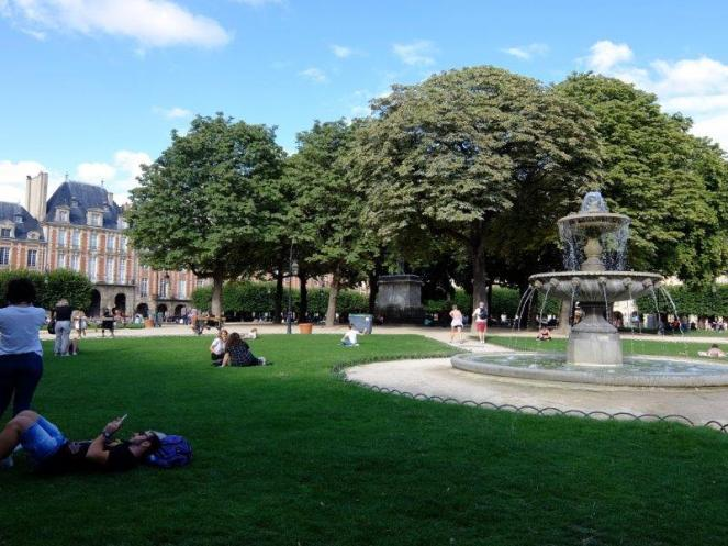 People sitting on the grass with fountain in center