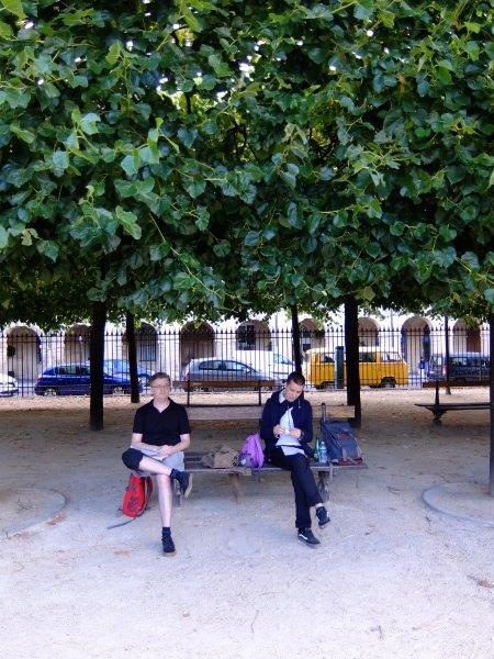 Two guys sitting on a bench underneath trees