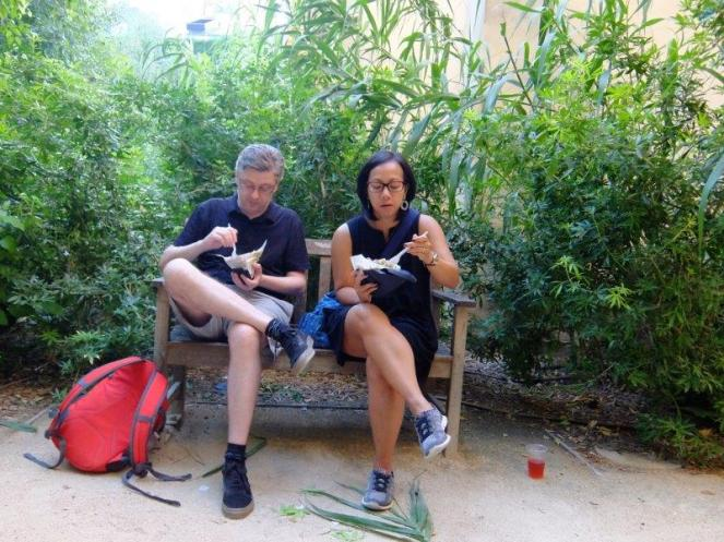 Man and woman eating kebab sandwich while sitting on a bench