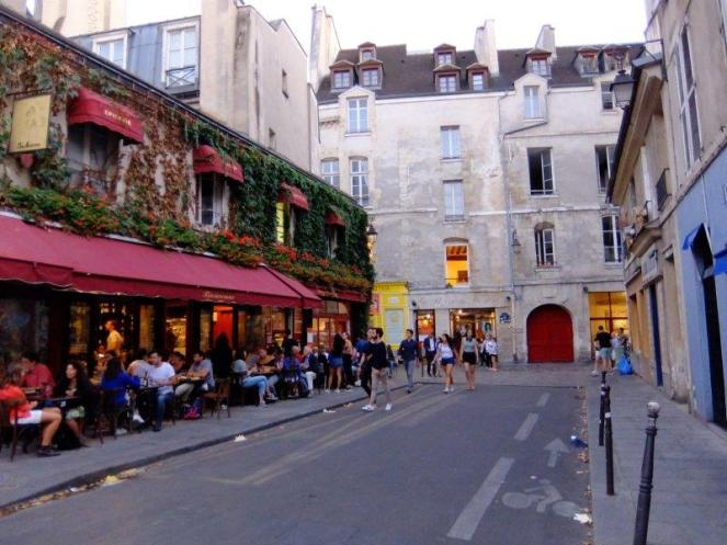 A street in Le Marais with a restaurant and tourists walking and eating