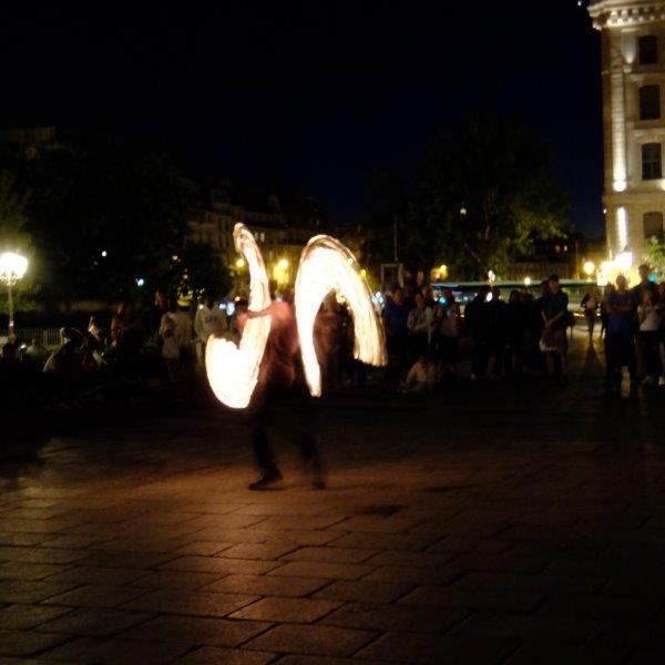 Street performance man with fire and people watching