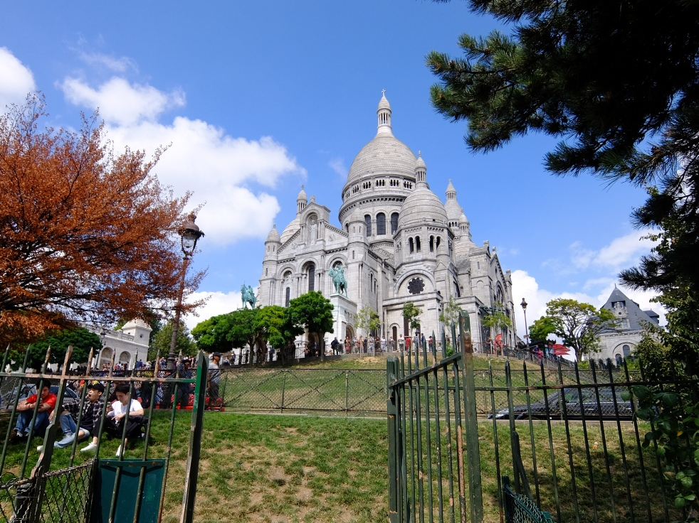 Sacre Coeur with blue sky against it and grass in front