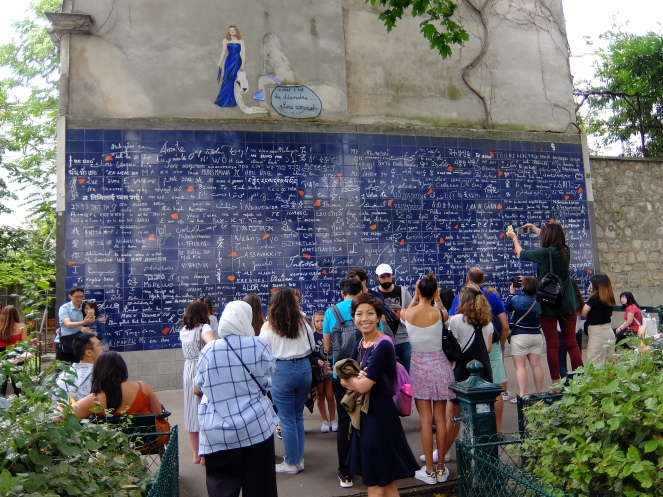 tourists in front of mur de je t'aime paris