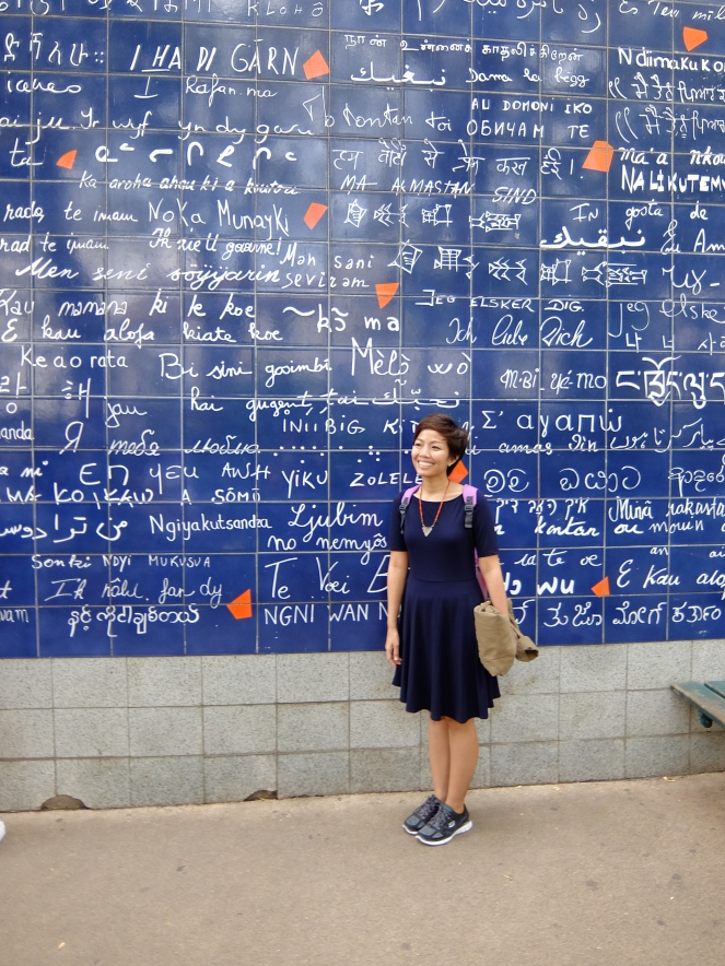 GIrl in front of blue wall with i love you in different languages