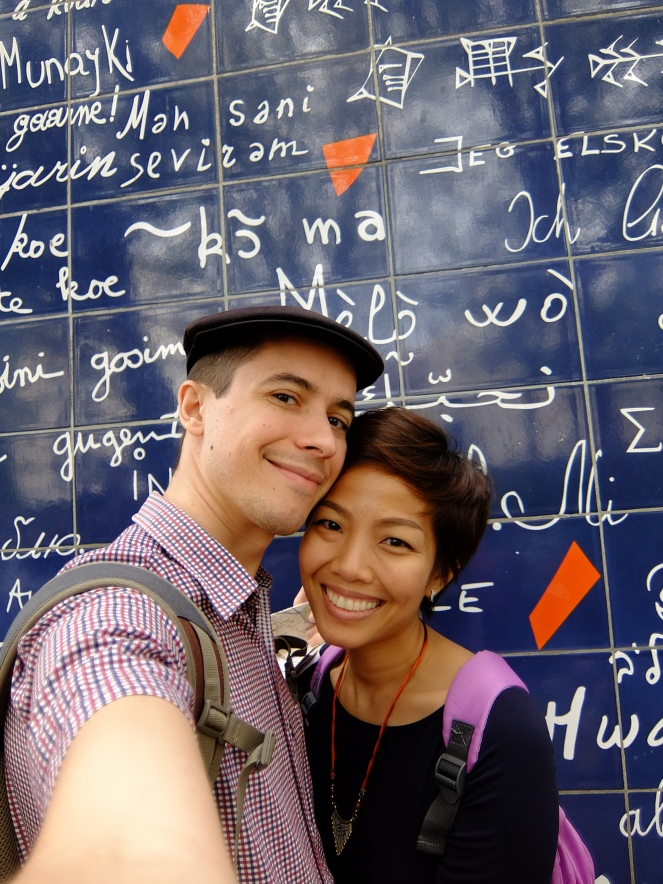 Couple in front of mur de je t'aime