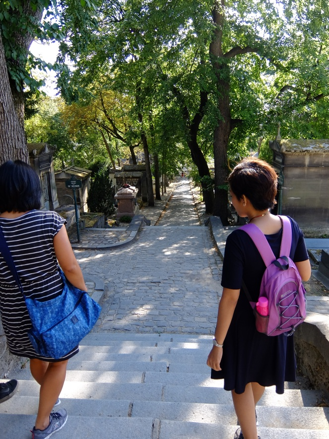 2 girls walking down a cemetery path