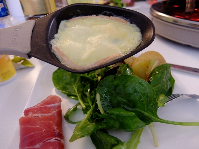 Raclette cheese melting on top of salad