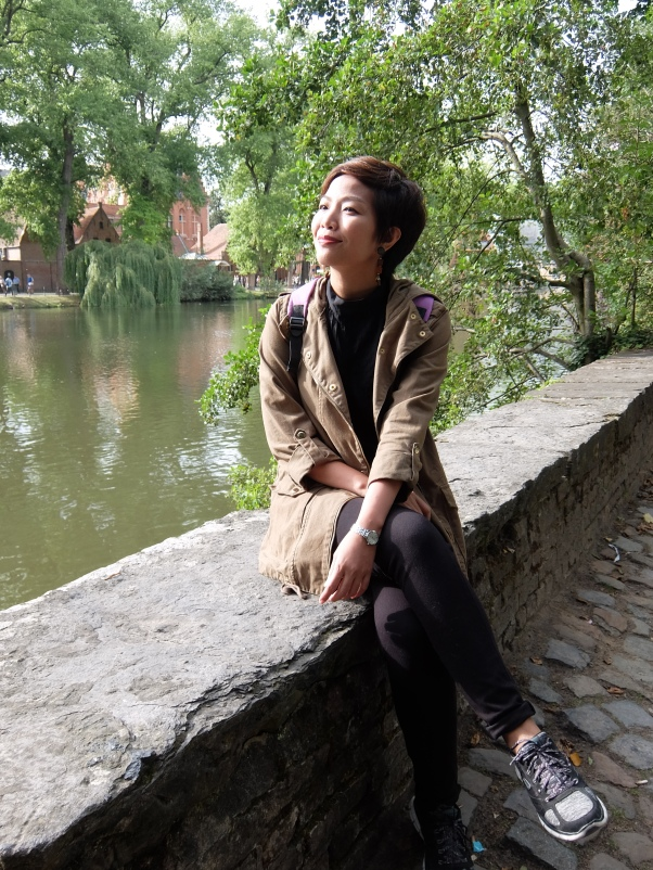 Female tourist sitting on stone border of Minnewater Bruges
