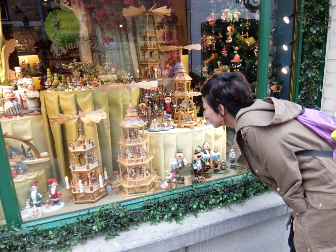 Girl looking through the glass window of wooden toy store