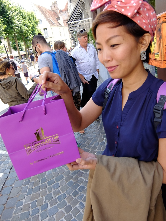 girl holding a purple paper bag with chocolates