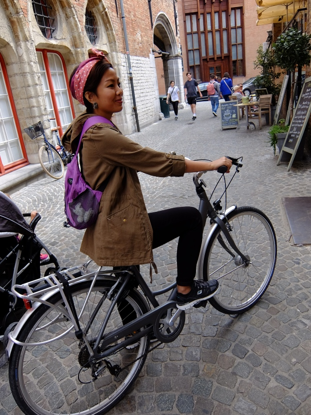 Girl with headband on bicycle in cobblestone street