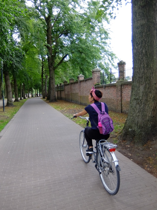 Girl with headband on bicycle in cobblestone street lined with trees