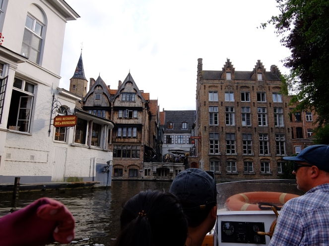 Old buildings in front of tourists crusing Bruges canal