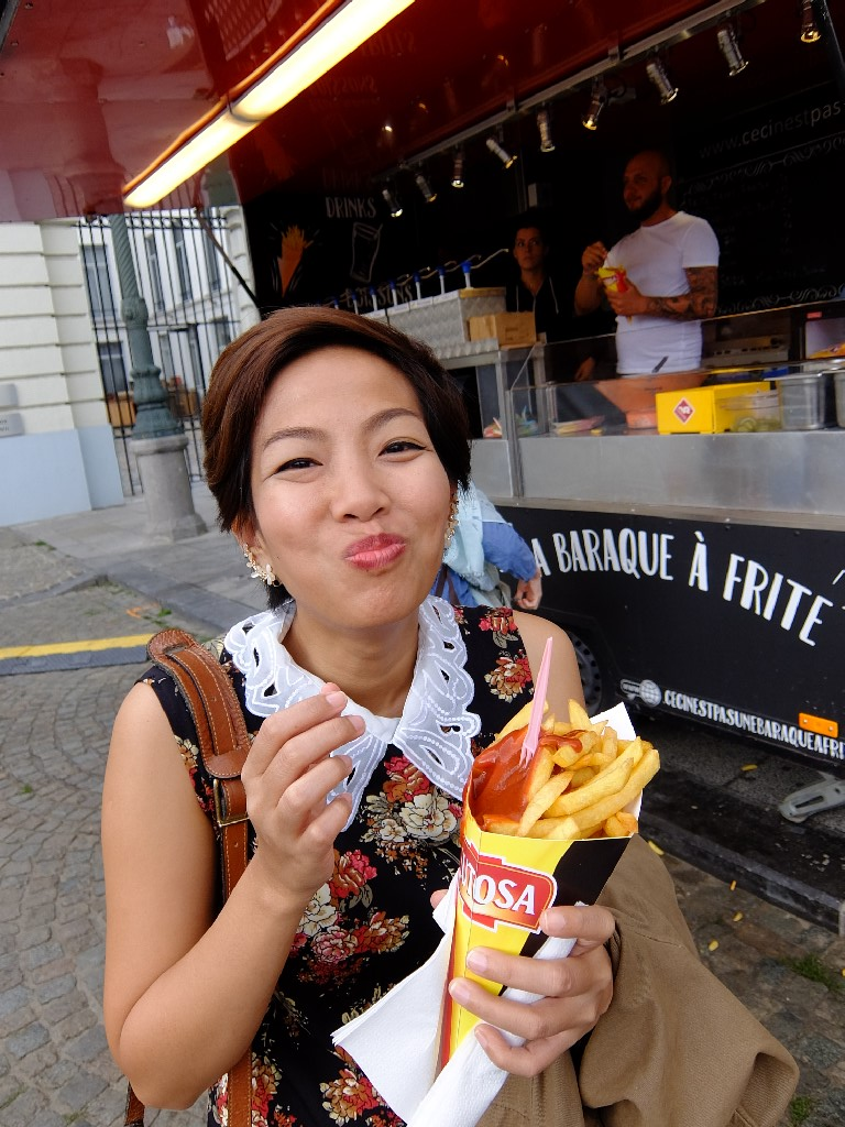 Girl eating Belgian fries with curry ketchup