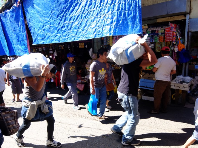 Two men carrying sacks on their back in Baguio market