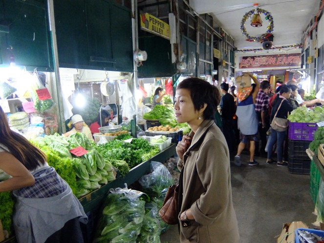 Girl in market looking at vegetables