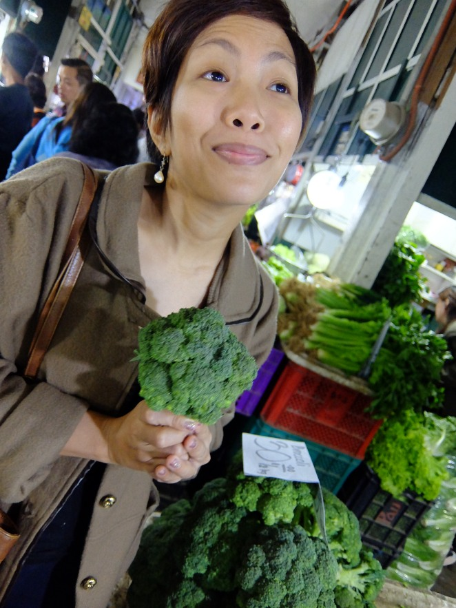 Girl in market holding a broccoli like it were flowers