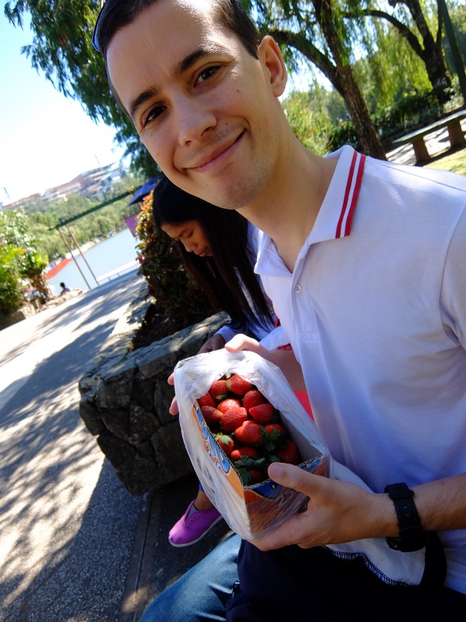 Guy with a box of strawberries sitting on park bench