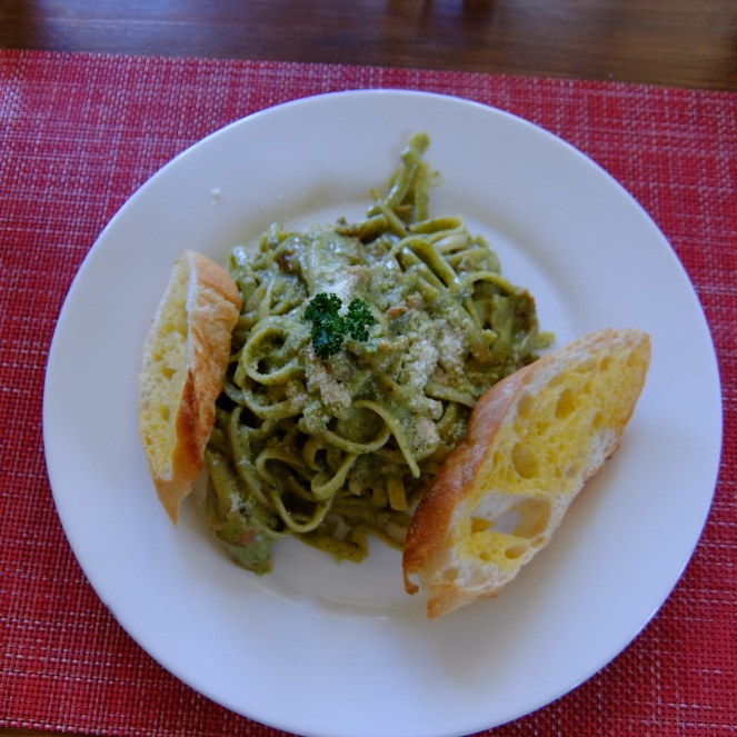 Plate of pesto carbonara with bread slices