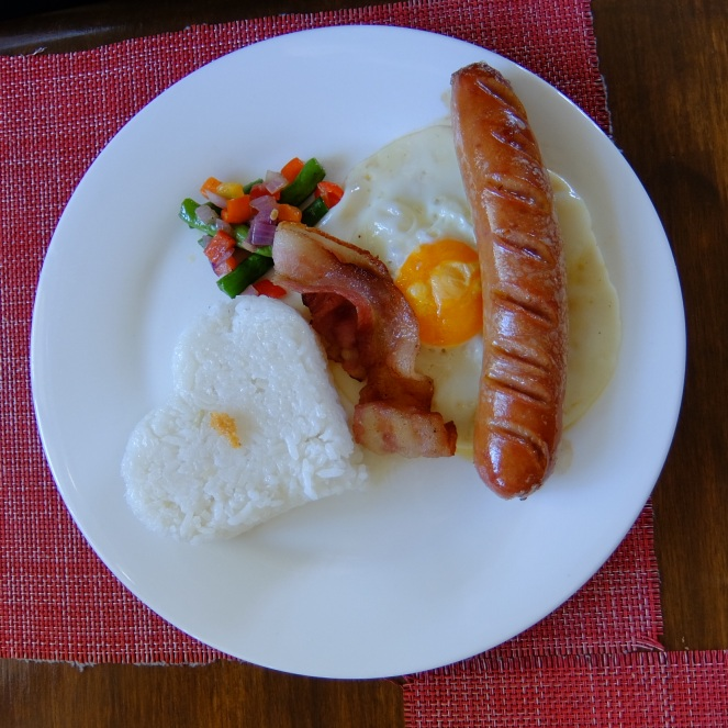 Plate of rice sausage bacon and egg