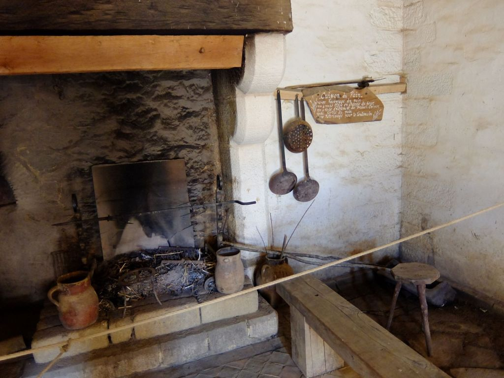 medieval fireplace with cooking tools hanging