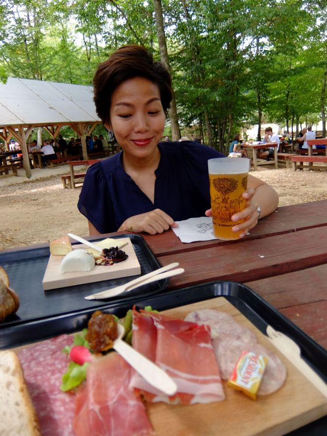 girl sitting at table with cheeses and cold cuts in and cider in front of her