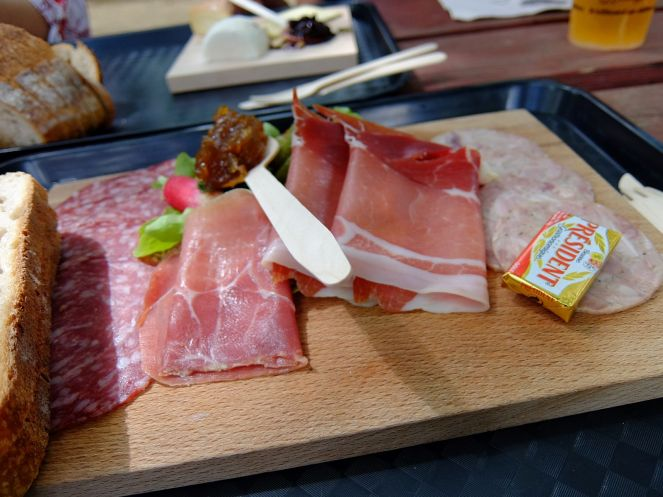 wooden board with cold cuts butter and bread on top