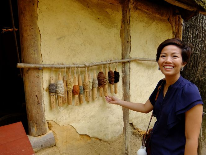 girl in front of spools of thread that are naturally pigmented