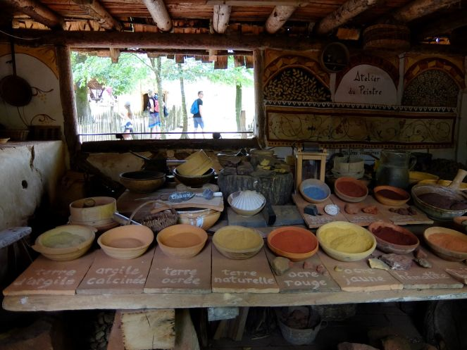 clay dishes containing natural pigments inside hut