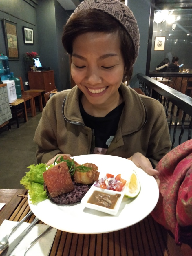 Girl holding a plate of rice with crispy pork