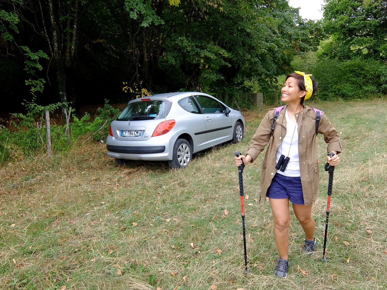Girl holding two hiking sticks in front of parked car