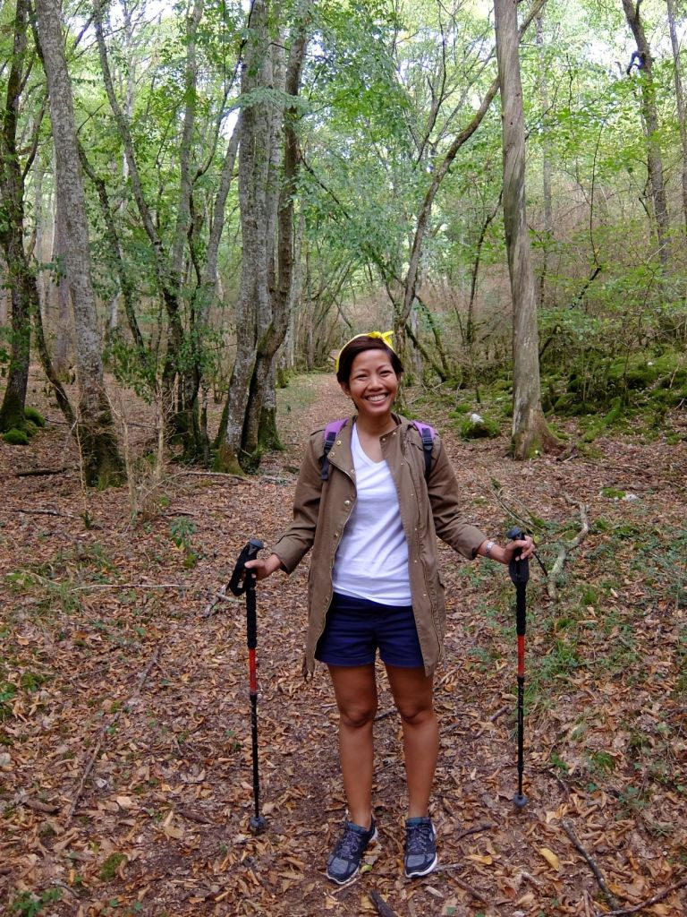 girl with two hiking sticks in the middle of forest path