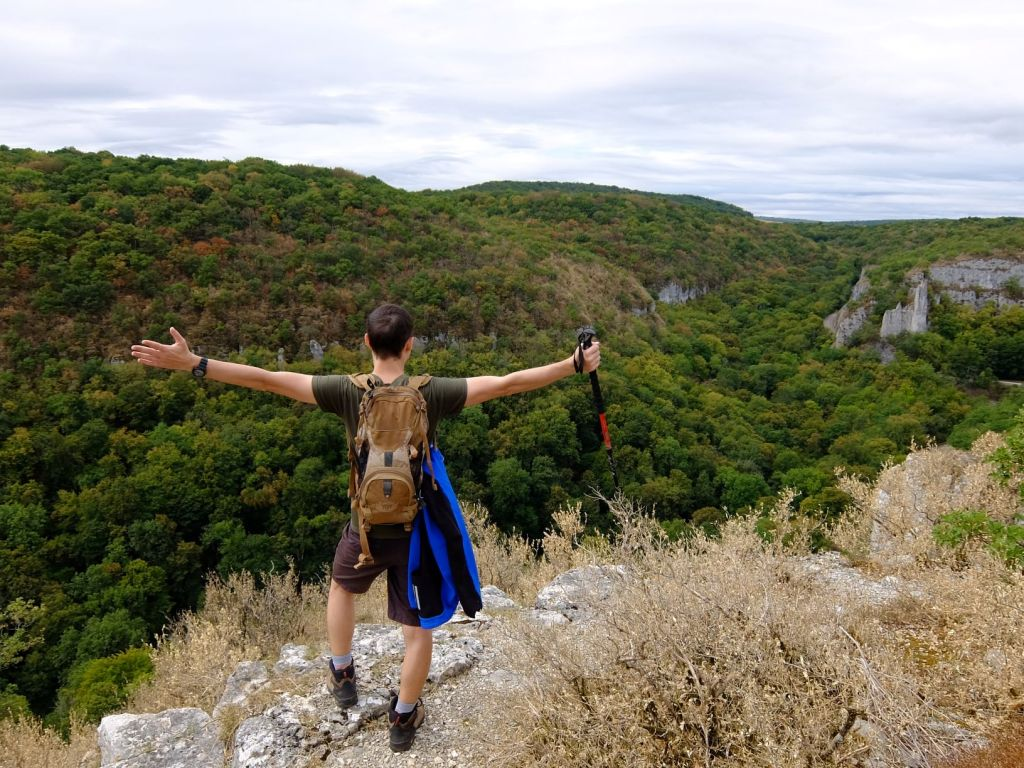 a guy standing on the edge of a cliff with arms outstretched