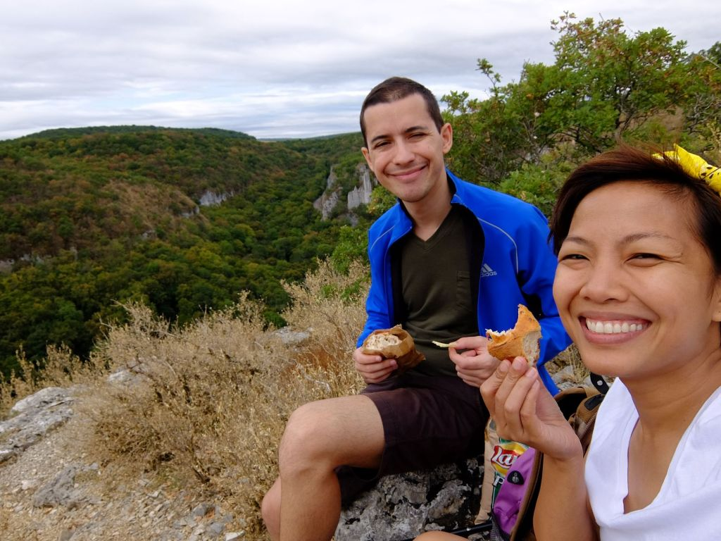 guy and girl on a cliff eating bread and smiling
