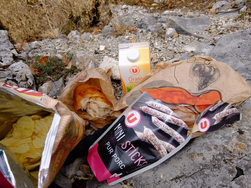 crisps, bacon bread, sausages and orange juice laid out on rocks
