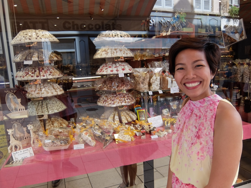 girl in front of a nougat shop display