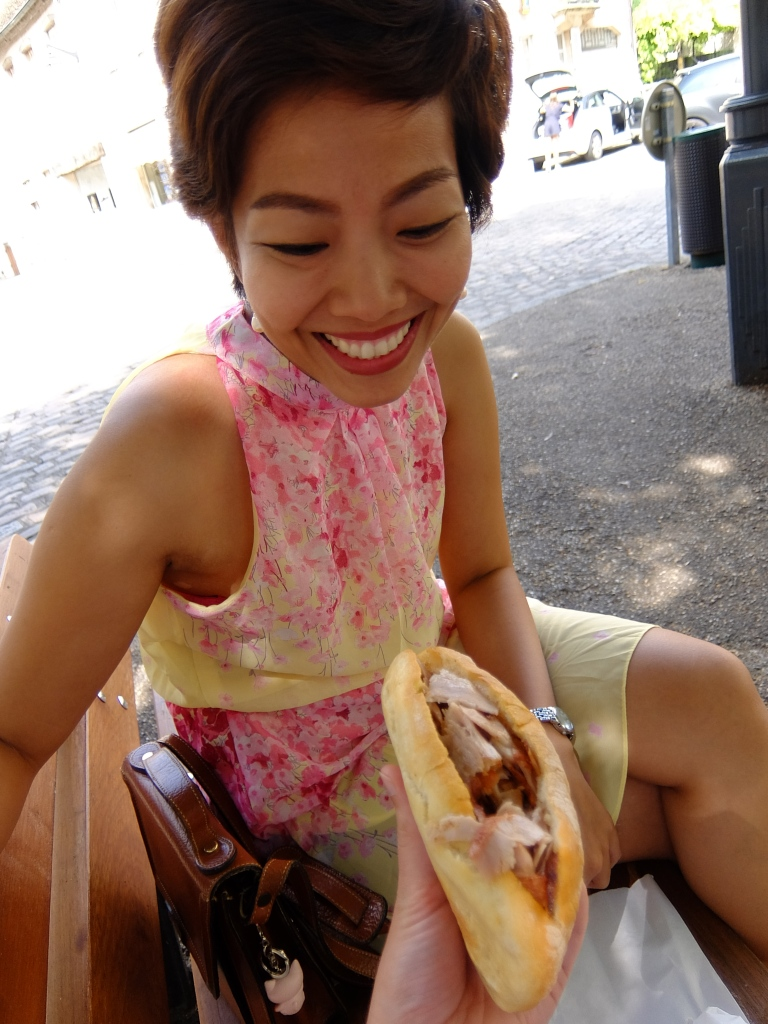 girl seated looking at kebab sandwich