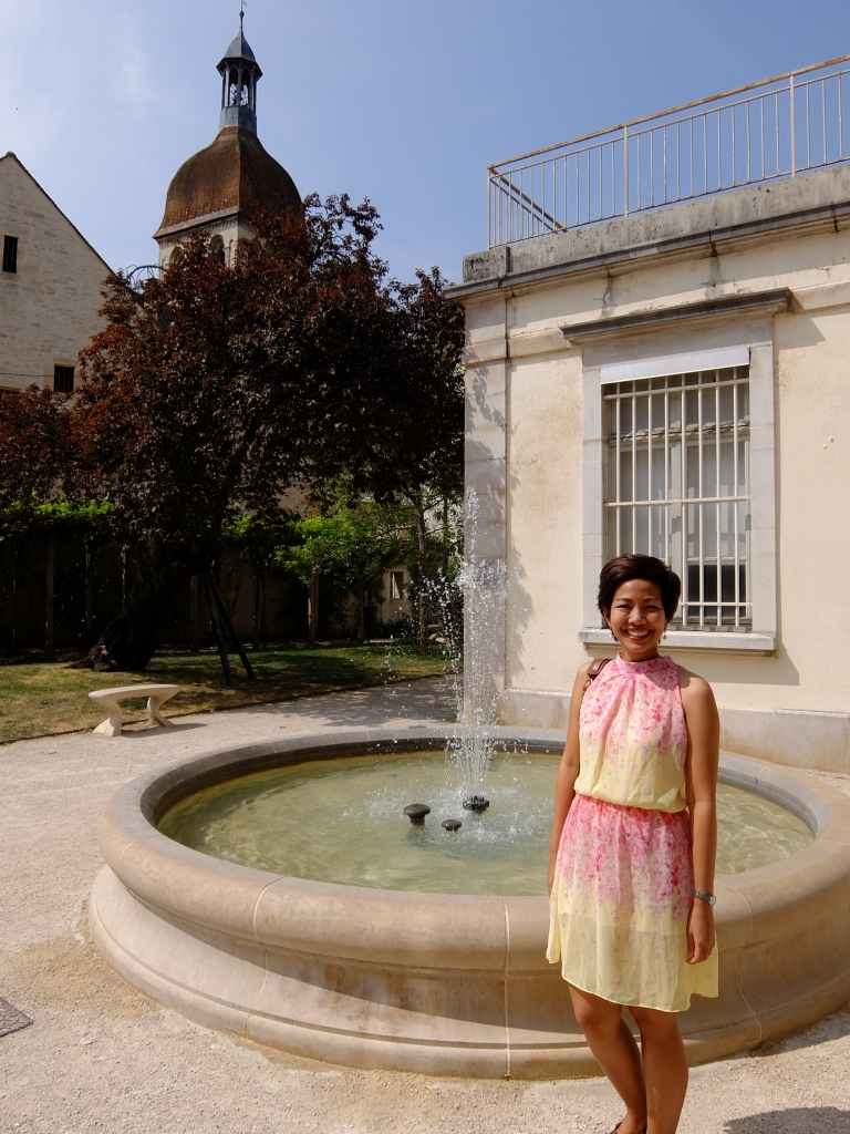 girl in front of a fountain in beaune france