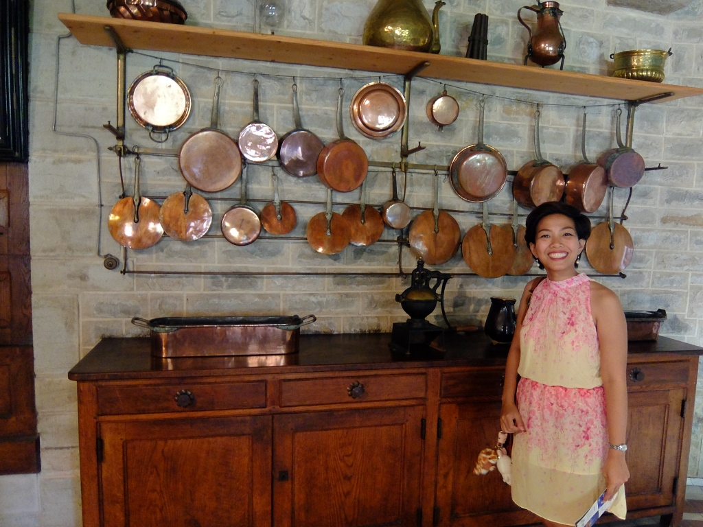 girl standing in front of old fashioned copper pots and pans