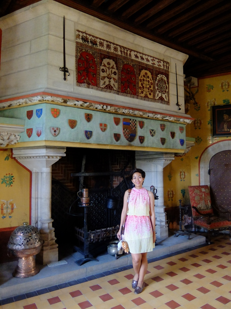 girl standing in front of a massive fireplace