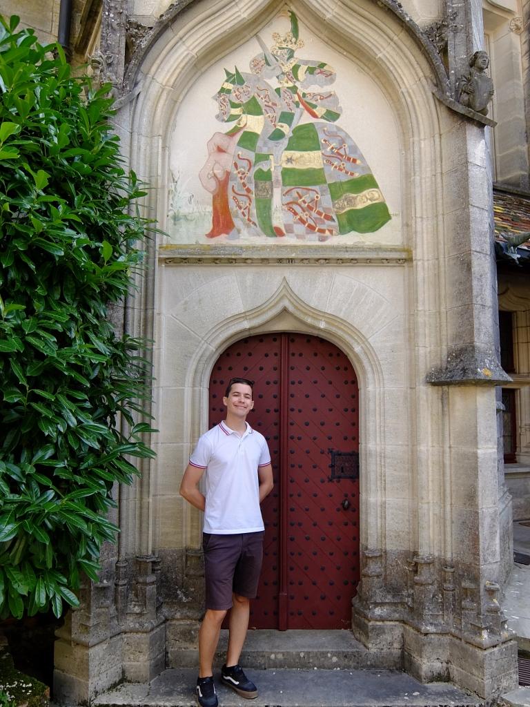 guy standing in front of door and coat of arms