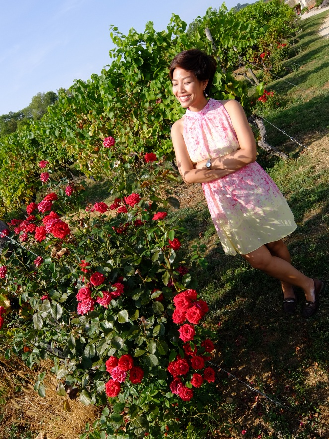 girl in front of rose bush and grape vines