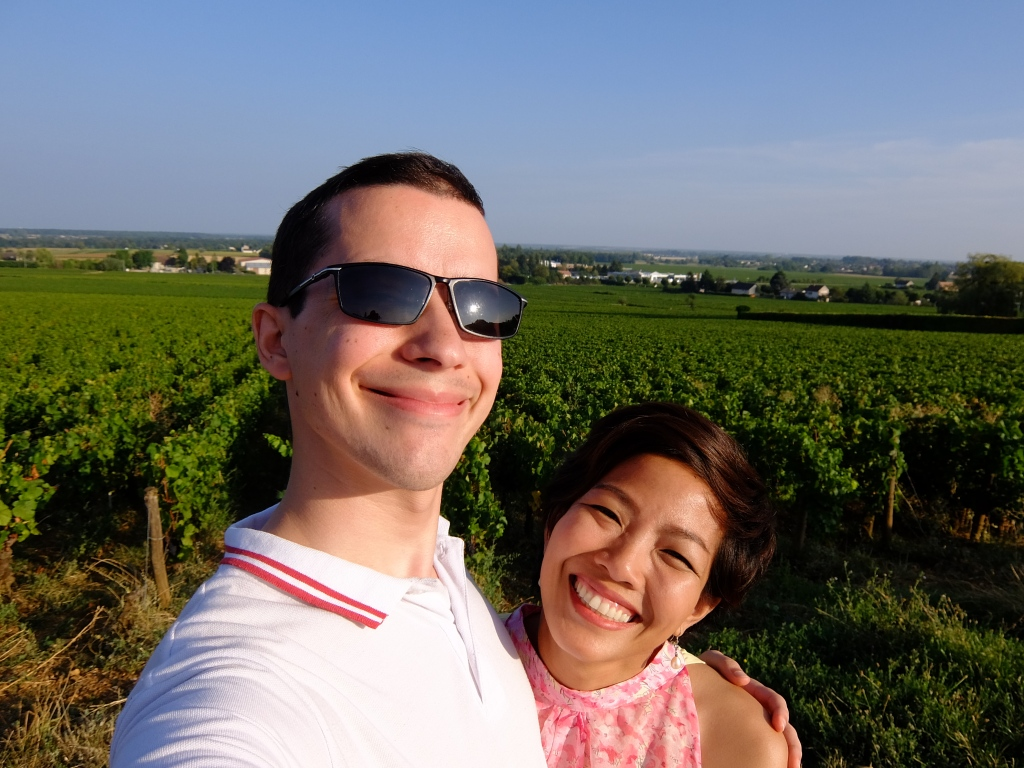 couple posing with grapevines behind