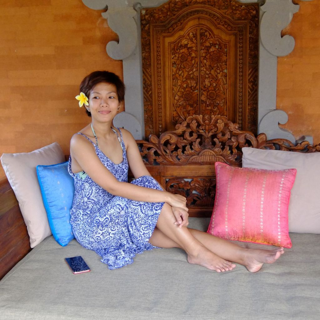 Girl with flower in hair sitting on a day bed