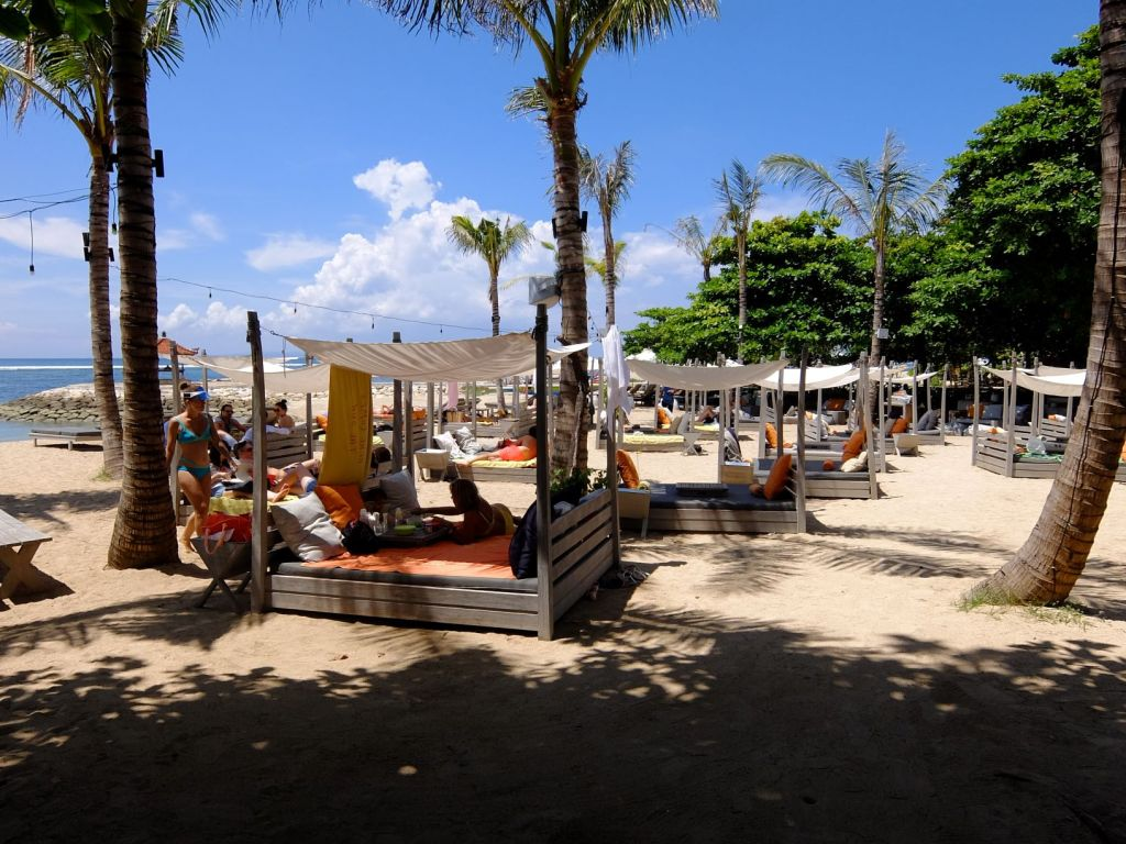 rows of daybeds with canopies by the beach